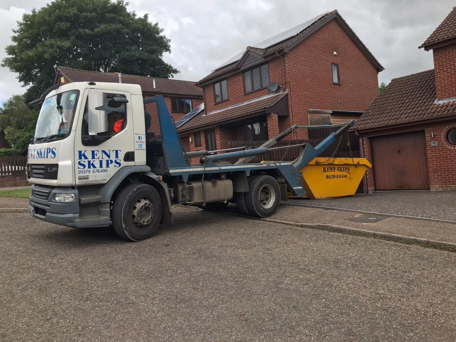 White and blue skip lorry on driveway of residential area
